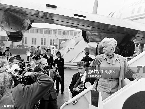 Stage Screen London England American film and movie actress Jane Mansfield surrounded by press photographers reporters as she walks down the steps...
