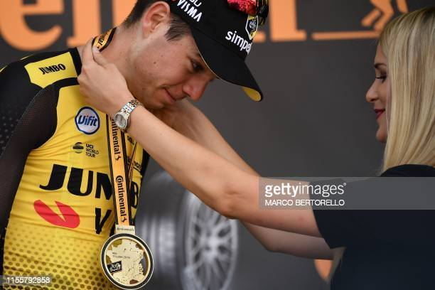 Stage winner Belgium's Wout van Aert receives his victory medal from an hostess as he celebrates on the podium of the tenth stage of the 106th...