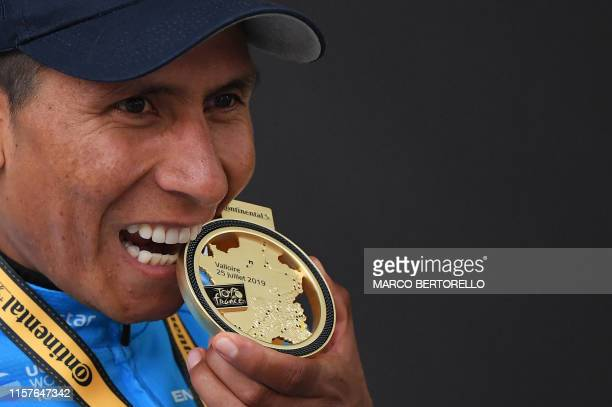 Stage winner Colombia's Nairo Quintana bites his medal as he celebrates his victory on the podium of the eighteenth stage of the 106th edition of the...