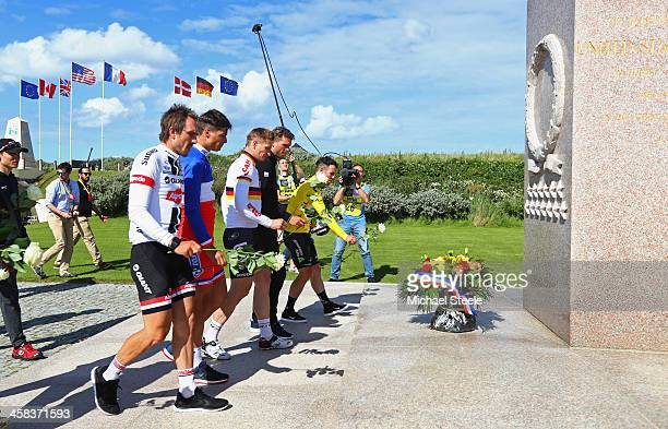 Stage winner Mark Cavendish of Great Britain and Team Dimension Data and fellow riders place flowers at a war memorial at Utah Beach after Stage One...