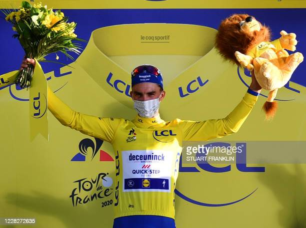 Stage winner Team Deceuninck rider France's Julian Alaphilippe celebrates his overall leader yellow jersey on the podium after winning the 2nd stage...