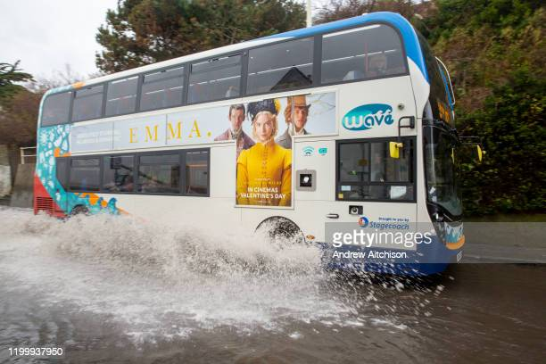 A stagecoach local bus drives down the A259 between Folkestone and Hythe which is flooded at Sandgate Kent on the south coast of England as Storm...