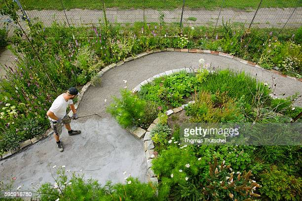 Staged Photo A man builds a path in his garden and rakes gravel on August 12 2016 in Berlin Germany