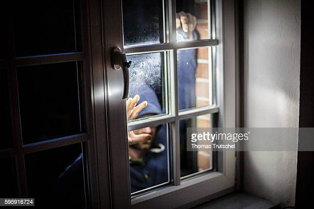Staged photo about burglary A man posing on a house window with a flashlight on August 11 2016 in Berlin Germany