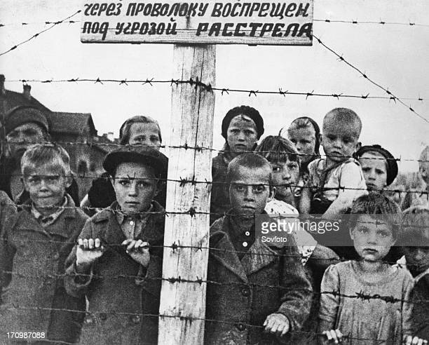 Staged photograph of Russian children behind barbed wire at a transfer camp, set up by Finnish forces of occupation in Petrozavodsk, Soviet East...