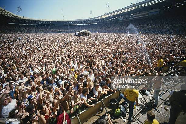 A stagehand cools down part of the crowd with a hosepipe at the Live Aid charity concert Wembley Stadium London 13th July 1985