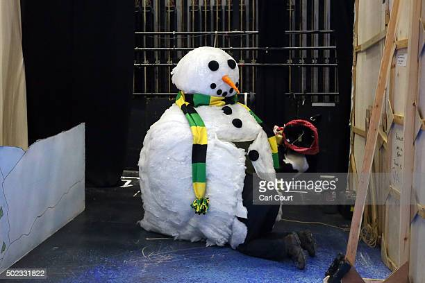 A stagehand makes adjustments inside a giant snowman before a performance of Jack and the Beanstalk at Hackney Empire on December 22 2015 in London...