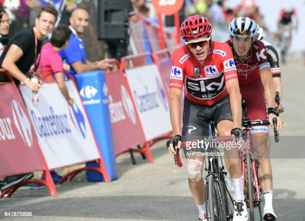 Stage's fourth placed and overall leader Sky's British cyclist Christopher Froome crosses the finish line of the 14th stage of the 72nd edition of La...