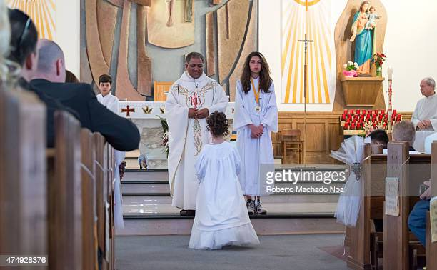 Stages of a Catholic First Communion ceremony Girl stands before priest near altar of Catholic church during mass dressed in white as others sit in...