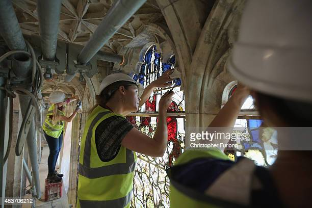 Stained glass conservators work on the first section of the restored 600yearold Great East Window of York Minster on August 12 2015 in York England...