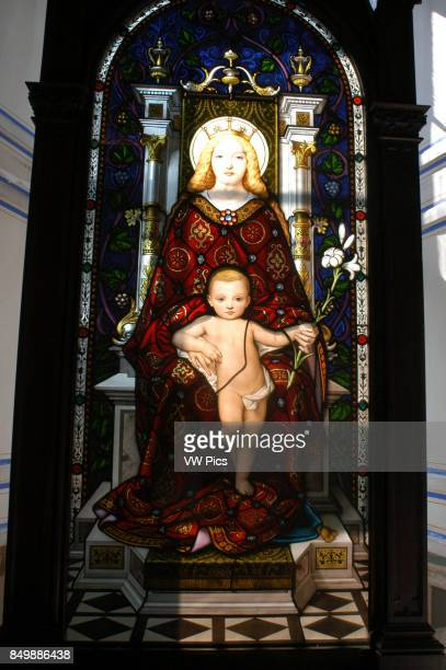 Stained glass image of Virgin and child Jesus backlit against window of gallery in Vatican Museum Vatican City Rome
