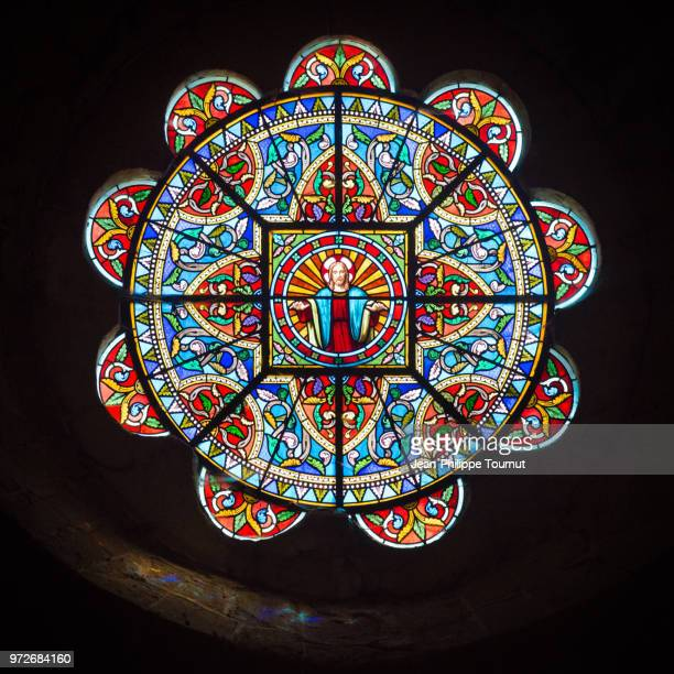 """stained glass rose window with the church of """"saint jacques le majeur"""", villefranche d'allier, allier, france - spirituality stock pictures, royalty-free photos & images"""