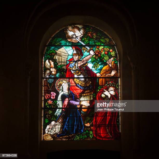 stained glass window depicting the martyrdom of saint valerie who was beheaded by her husband, monastery of st. valerie in chambon sur voueize, abbatiale sainte valérie, creuse, france - abadia igreja - fotografias e filmes do acervo
