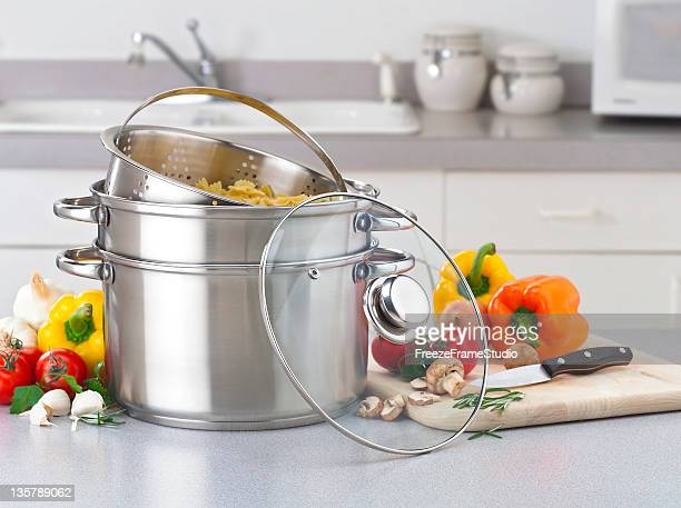 Stainless pasta pot on kitchen counter with fresh vegetables