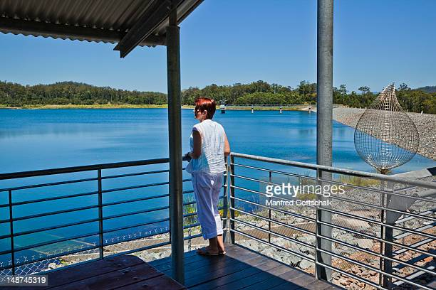 stainless steel rod sculpture 'the drip' by peter allison at cowarra off-creek dam, with female visitor in foreground. - port macquarie stock pictures, royalty-free photos & images