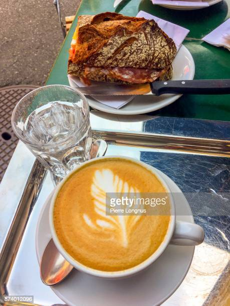 Stainless steel tray with Italian style cappuccino, a glass of water, and salami sandwich made in sourdough country bread.