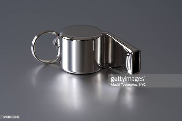 Stainless steel whistle on a silver background.