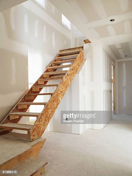 Staircase in drywalled hallway
