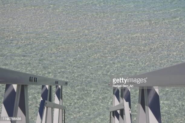 staircase rails into a clear sea water - rafael ben ari - fotografias e filmes do acervo