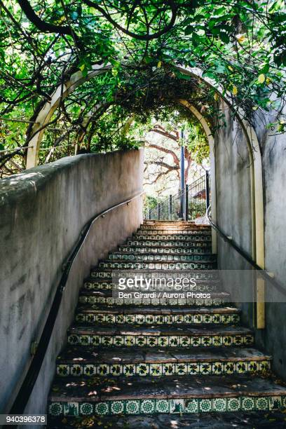 Stairs lined with tile and covered with an awning of plants lead up from the San Antonio river walk to La Villita.