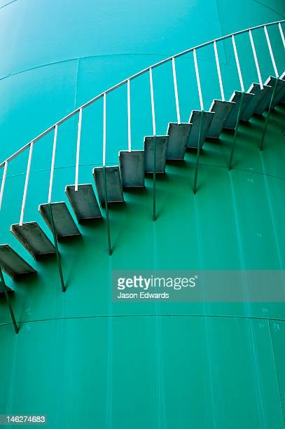 Stairs spiral around the wall of a turquoise airport deluge water tank.