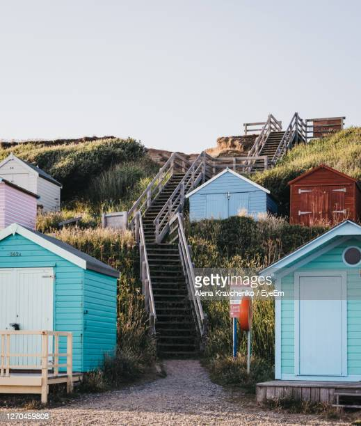 stairs to the beach between colourful beach huts in milford on sea, uk. - multi coloured stock pictures, royalty-free photos & images