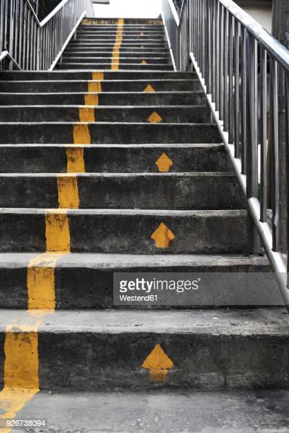 stairs with yellow arrows - arrow stock photos and pictures