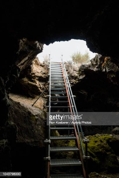 stairway leading up and out of cave - koeberer stock photos and pictures