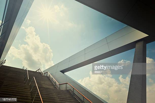 A stairway leading up to blue sky with sun over light cloud