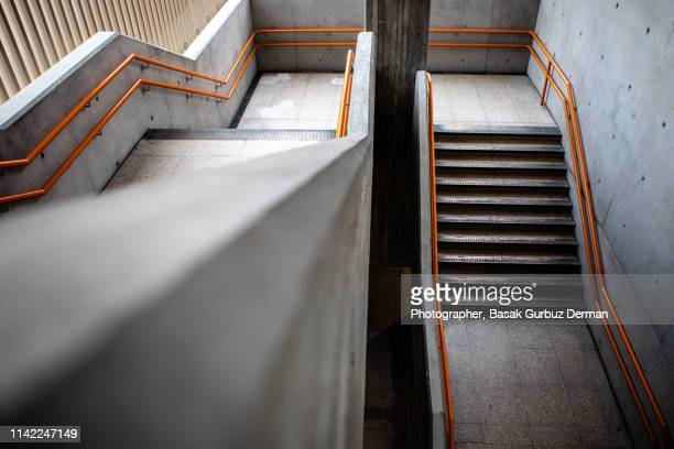 Stairways with concrete walls and orange bannisters