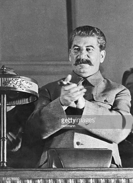 Stalin applauds a speaker discussing Stalin's report on the draft of the new constitution of the USSR during the eighth Soviet congress