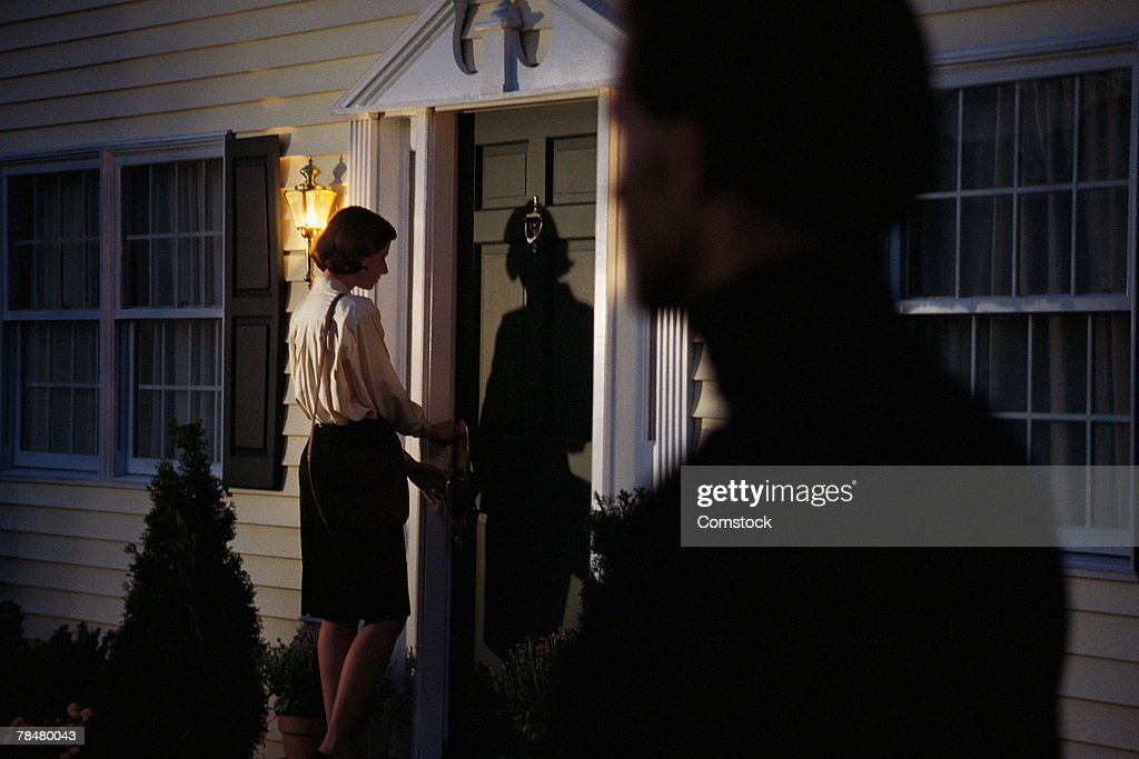 Stalker spying on woman at front door : Stock Photo
