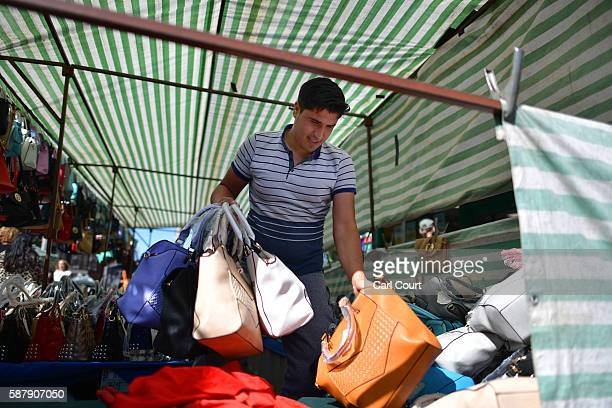 A stall holder arranges handbags for sale in Walthamstow market on August 9 2016 in London England Walthamstow Market in north east London is...