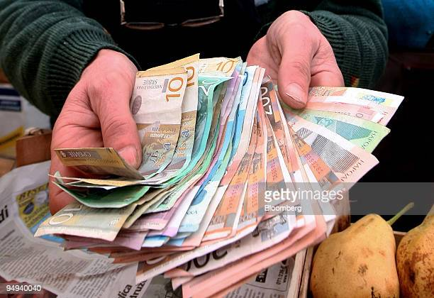 A Stall Holder Displays Varying Bank Notes Of The Local Currency Serbian Dinar While In