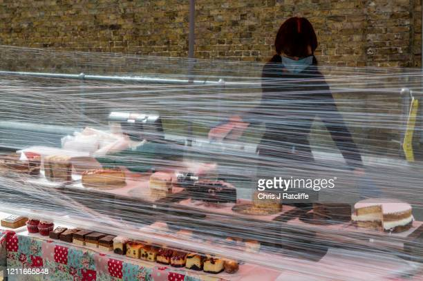 Stall holder, Freya Storch, wears a face mask and gloves as she works on her cake stall behind a protective film barrier at Blackheath Farmers Market...
