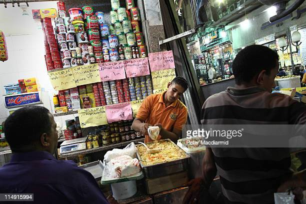 A stall holder prepares food for sale at Ataba market on May 28 2011 in Cairo Egypt Protests in January and February brought an end to 30 years of...