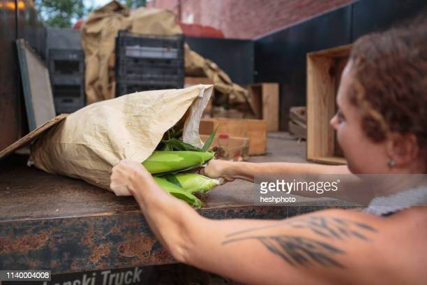 stall holder unloading sacks of organic food for store - heshphoto stock pictures, royalty-free photos & images