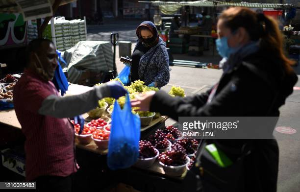 Stall holder wearing PPE including a face mask and gloves as a precautionary measure against COVID-19, serves customers fruit and vegetables from a...