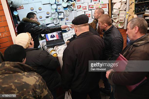 Stall holders and members of the public gather round a laptop to watch an address by Russia's President Vladimir Putin on a market stall on March 18...