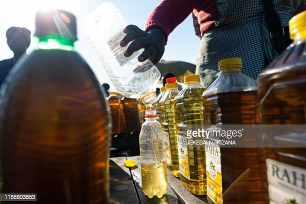 Stall owner pours out a measure of cooking oil into a smaller more affordable bottle for resale at Harare Mbare Musika marketplace on July 15, 2019....