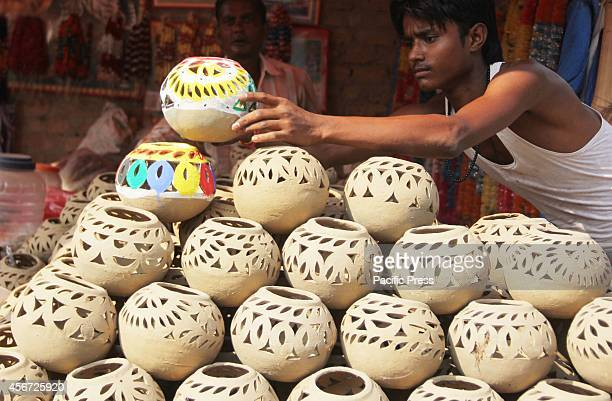 Stall owners prepare earthen lamps called Dhaddiya usually bought by women for them to offer prayers for their brothers' long life in a market at...