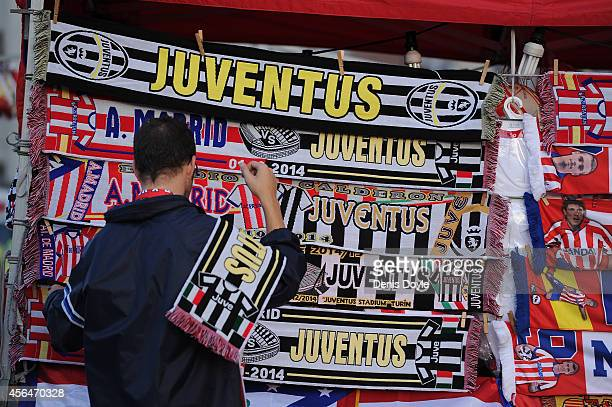 A stall seller fixes Club Atletico de Madrid and Juventus scarves outside the Vicente Calderon Stadium before the UEFA Champions League Group A match...