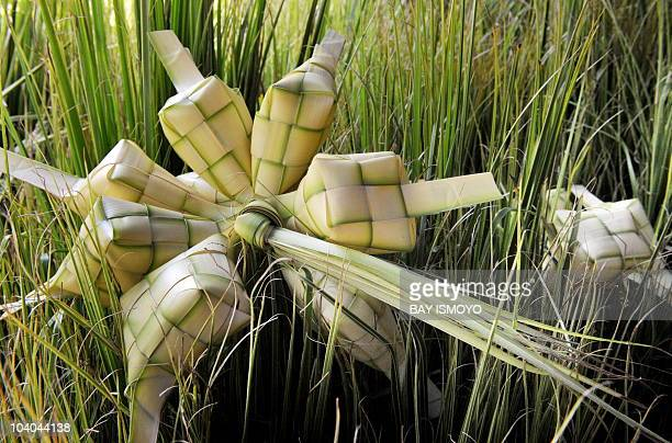 A stall vendor weaves a 'ketupat' a traditional weaved pocket made from coconut leaves used to cook rice cakes in and as a seasonal decoration in...