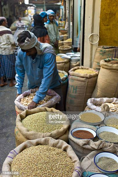 Stallholder with coriander seeds and dried mango skins on sale at Khari Baoli spice and dried foods market Old Delhi India#13#10