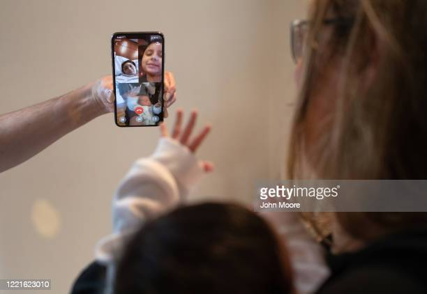 Stamford Elementary school teacher Luciana Lira holds baby Neysel then 2 1/2 weeks while showing the newborn via Zoom to Zully a Guatemalan asylum...