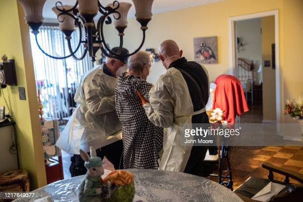 Stamford EMS medics wearing personal protective equipment assist a woman in her apartment on April 02 2020 in Stamford Connecticut The medics came...