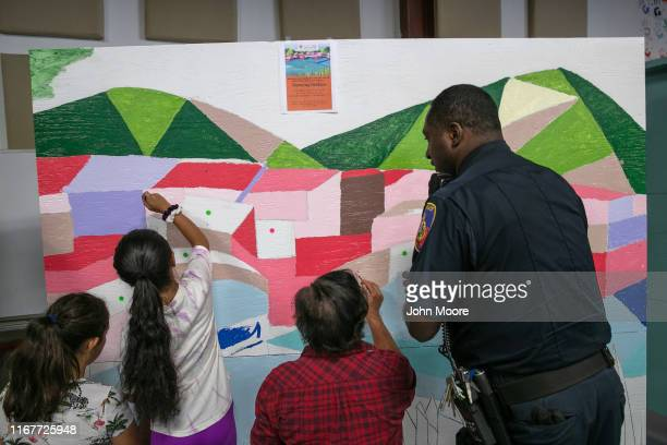 Stamford Police officer Ramon Gipson paints a mural with immigrant families during a communitybuilding event on August 10 2019 in Stamford...