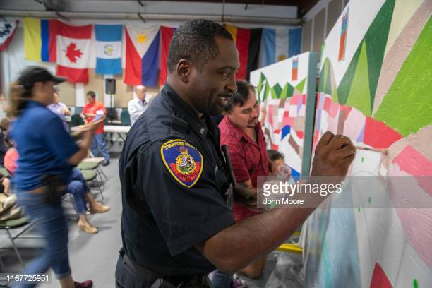 Stamford Police officer Ramon Gipson paints a mural with immigrant families during a community-building event on August 10, 2019 in Stamford,...