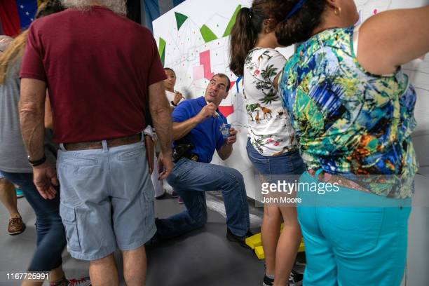 Stamford policeman paints a mural with immigrant families during a communitybuilding event on August 10 2019 in Stamford Connecticut The event...