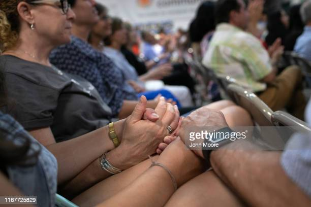 Stamford residents hold hands during a moment of silence at a community event welcoming immigrants on August 12, 2019 in Stamford, Connecticut. State...